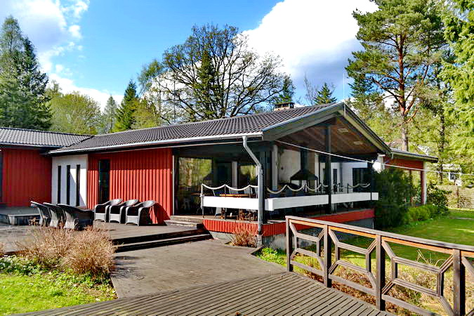 Blick auf das Haus mit großen Fensterfronten zum See und großer Veranda mit Seeblick