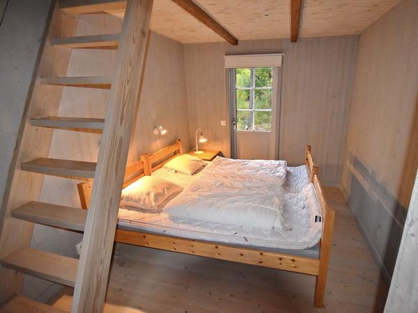 Schlafzimmer mit Doppelbett und Treppe zum Schlafboden