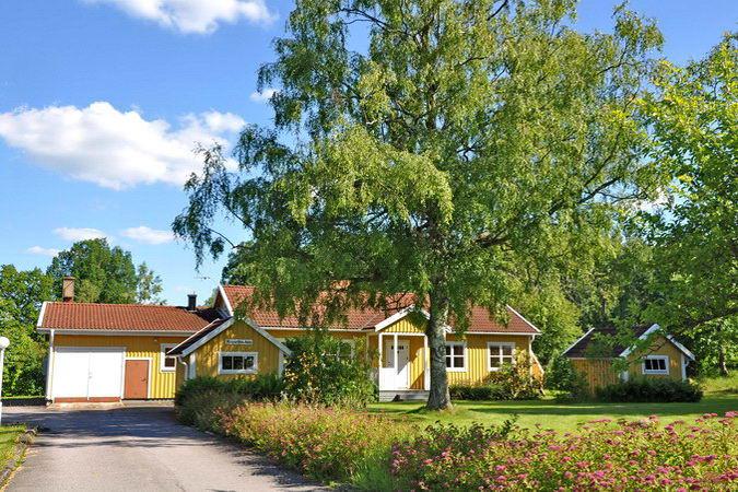 Blick über das Grundstück auf das Haus mit seinen Nebengebäuden