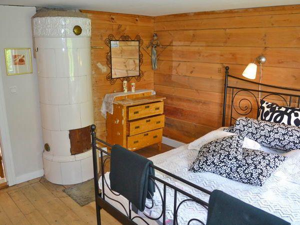 Schlafzimmer mit Doppelbett und dekorativem Kachelofen