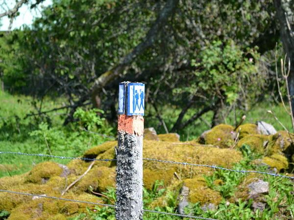 Markierung des Wanderweges am Grundstücksrand