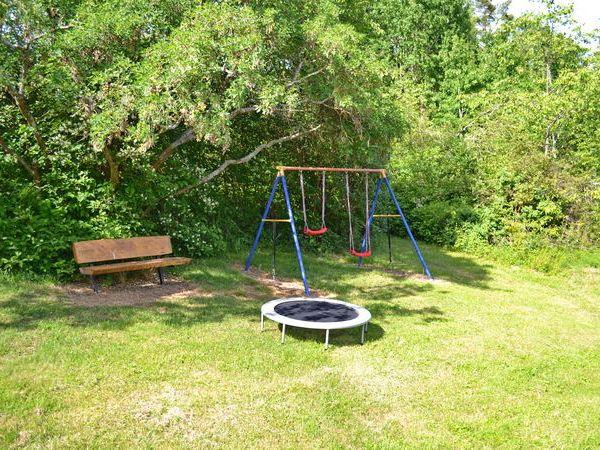 Blick in den Garten mit Schaukel und Kindertrampolin