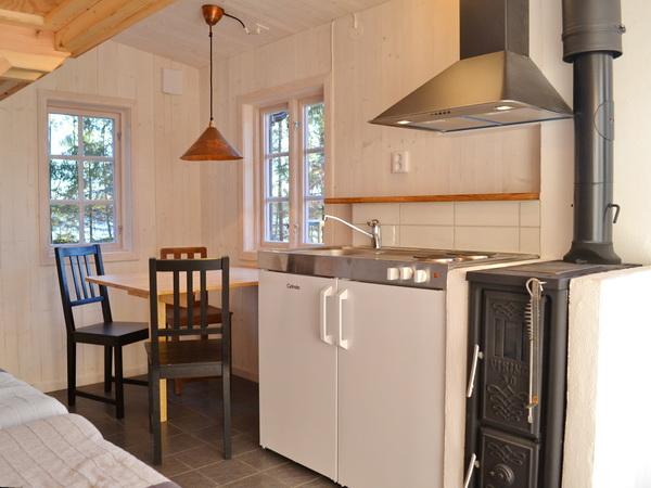 kombinierter Wohn- und Schlafraum mit 4 Betten, Esstisch und Pantryküche