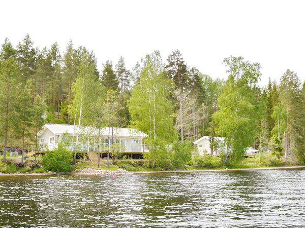 Blick vom See auf das Haus mit Nebengebäude