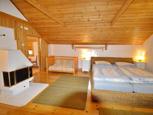 Schlafzimmer 1 mit Doppelbett und Kinder-Gitterbett