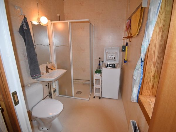 Badezimmer mit WC, Waschmaschine und Dusche im Erdgeschoss