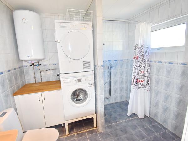 Badezimmer mit WC, Waschmaschine, Trockner und Dusche