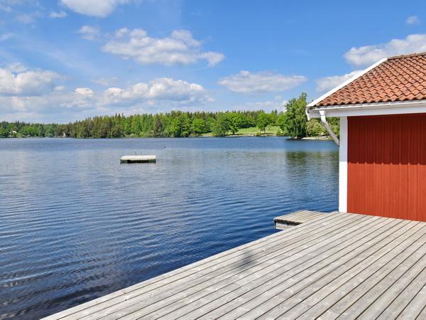 Bootshaus mit hauseigenem Ruderboot und Terrasse am See